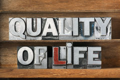 Quality of life tray. Quality of life phrase made from metallic letterpress type on wooden tray Royalty Free Stock Photography