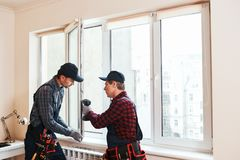 Quality light. Construction workers installing new window in house. Together stock photos