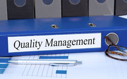 Quality Management binder. With a ballpoint pen and eyeglasses on an office desk Stock Photo