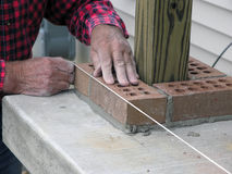 Quality, Master Bricklayer uses Level Line. Skillful master bricklayer uses level line to ensure quality royalty free stock photography