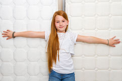 Quality mattress. Smiling young girl with orthopedic mattress. Quality mattress Stock Image
