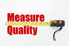 Quality measurement concept. Measuring tape over the words measure and quality on white background Stock Photo