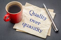 Quality over quantity inspirational reminder note. Handwriting on a napkin with cup of coffee against gray slate stone background Royalty Free Stock Images