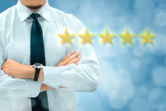 Quality, performance review, evaluation and classification ranking concept. Businessman silhouette in background. Five yellow. Glowing stars icons in the stock photos