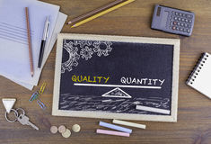 Quality Quantity Balance. Chalkboard on wooden office desk.  Royalty Free Stock Images
