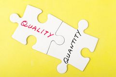 Quality or quantity. Quality and quantity words written on two pieces of puzzle Royalty Free Stock Photography