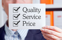Quality, Service and Price. White card held in the hand of a businesswoman bearing text and tick boxes, 'Quality, Service and Price' with ticks in all three Stock Photo
