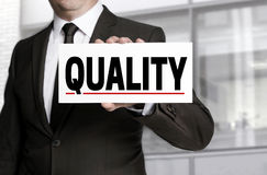 Quality sign is held by businessman Stock Image