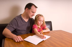 Quality Time. Father teaching young daughter to write; caucasian models, lots of copy space Royalty Free Stock Photography