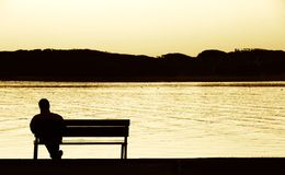 Quality time. Man taking a break in life, siting by the river Royalty Free Stock Photography