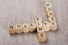 Quality; time and money cubes arranged on table Stock Photography