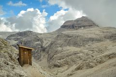 Quality time in wooden outhouse with view on Piz Boe in Dolomite stock photography