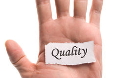 Quality word in hand. Word on piece tear paper Stock Photo