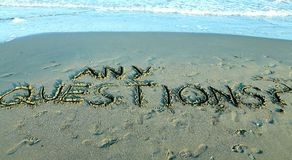 QUALSIASI DOMANDE scritte sulla sabbia del mare Fotografie Stock