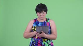 Quando de pensamento da mulher asiática excesso de peso nova feliz usando a tabuleta digital filme