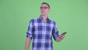 Quando de pensamento do homem novo feliz do moderno usando o telefone vídeos de arquivo