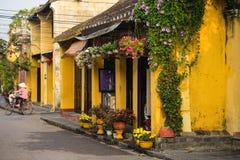 Quang Nam, Вьетнам - 2-ое апреля 2016: Старый постаретый дом с желтыми стеной и цветочными горшками против задействуя женщины на  Стоковые Изображения RF