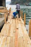 Quang Ninh, Βιετνάμ - 22 Μαρτίου 2015: Ο βιετναμέζικος εργαζόμενος κάνει την ξύλινη βάρκα Bai TU στο μακρύ κόλπο, μακριά πόλη εκτ Στοκ Φωτογραφίες