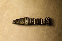 QUANTITIES - close-up of grungy vintage typeset word on metal backdrop Stock Photos