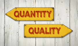 Quantity or Quality. Direction signs on a wooden wall - Quantity or Quality Stock Images