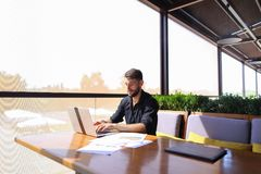 Quantity surveyor working at cafe table with papers and laptop. Tired quantity surveyor working at cafe table with diagram and statistic documents. Persistent Royalty Free Stock Photo