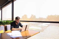 Quantity surveyor working at cafe table with papers and laptop. Tired quantity surveyor working at cafe table with diagram and statistic documents. Persistent Royalty Free Stock Photos