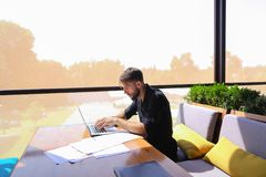 Quantity surveyor working at cafe table with papers and laptop. Tired quantity surveyor working at cafe table with diagram and statistic documents. Persistent Royalty Free Stock Images