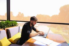 Quantity surveyor working at cafe table with papers and laptop. Tired quantity surveyor working at cafe table with diagram and statistic documents. Persistent Royalty Free Stock Photography