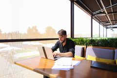 Quantity surveyor working at cafe table with papers and laptop. Tired quantity surveyor working at cafe table with diagram and statistic documents. Persistent Stock Photography