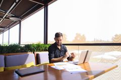 Quantity surveyor working at cafe table with papers and laptop. Tired quantity surveyor working at cafe table with diagram and statistic documents. Persistent Royalty Free Stock Image