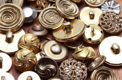 Quantity of vintage metal buttons on wooden surface Royalty Free Stock Photos