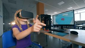 Quantorium laboratory with a teen girl being in virtual reality glasses and passing hands stock footage