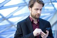 Uomo d'affari dentro l'ufficio che guarda su un telefono cellulare Fotografia Stock Libera da Diritti
