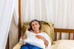 Quaranta sul telefono su letto a baldacchino immagine stock libera da diritti