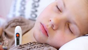 Quarantine, flu epidemic. A close-up, an electronic thermometer, changes in values and figures are visible, the body temperature rises. Sad, sleeping face of a stock footage