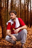 Homem do corredor que tem um resto após o exercício movimentando-se na floresta Fotos de Stock