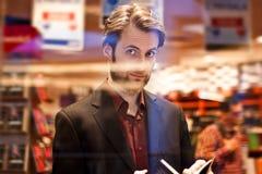 Homem elegante que está a livraria interna que lê um livro Imagem de Stock