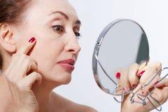 Quarenta anos de mulher adulta que olha enrugamentos no espelho Injeções da cirurgia plástica e do colagênio composição Cara macr Fotografia de Stock Royalty Free