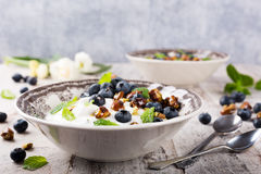 Quark with blueberries, pistachios and mint. Healthy breakfast, quark with blueberries, pistachios and mint on light wooden background Royalty Free Stock Image
