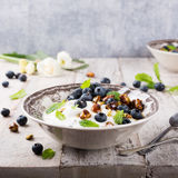 Quark with blueberries, pistachios and mint. Healthy breakfast, quark with blueberries, pistachios and mint on light wooden background Stock Photo