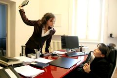 Quarrel 18. Two woman having an angry confrontation in a office Royalty Free Stock Photography