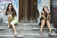 Two young fashion girls in conflict on the steps. Two young fashion girls in conflict sitting on the steps Stock Image