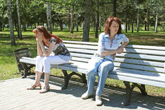 Quarrel. Two young women on a bench in park Stock Image