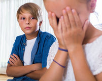 Quarrel between brother and small sister. In domestic interior. Focus on boy Stock Images
