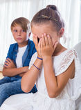 Quarrel between brother and small sister. In domestic interior. Focus on girl Stock Images