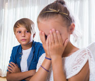 Quarrel between brother and small sister. Quarrel between russian brother and small sister in domestic interior. Focus on boy Royalty Free Stock Image
