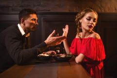 Quarrel of couple in restaurant, bad relationship. Quarrel of young couple in restaurant, bad relationship. Elegant women in red dress and her men eating in cafe royalty free stock images