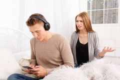 The quarrel of a guy and a girl. Quarrel of a guy and a girl on a white background room guy in headphones girl yelling at him Stock Images