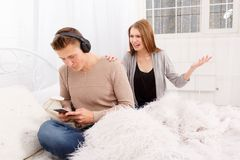 The quarrel of a guy and a girl. Quarrel of a guy and a girl on a white background room guy in headphones girl yelling at him Royalty Free Stock Image