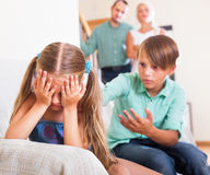 Quarrel between kids. Little sister and brother abusing each other, a parents standing near them at home Royalty Free Stock Photo